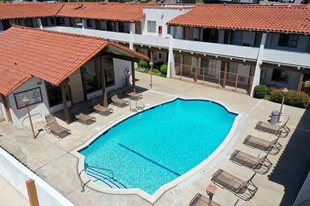 Apartments in Tustin, CA - Arial View of Las Casas Sparkling Swimming Pool Surrounded By Lounge Seating