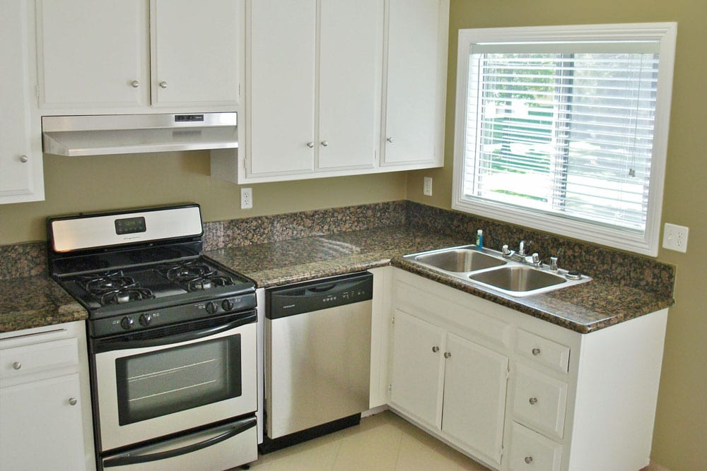 Tustin CA Apartments - Las Casas Apartments -Spacious Kitchen With Granite Countertops, White Cabinets, and Stainless Steel Appliances